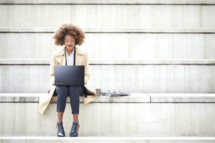 Junge Geschäftsfrau mit Laptop auf einer Treppe
