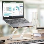 Zu sehen ist ein Notebook, dass auf einem erhöhten Standfuß auf einem Schreibtisch steht. Der Standfuß ermöglicht einen komfortablen Blick auf das Notebook für den Nutzer.